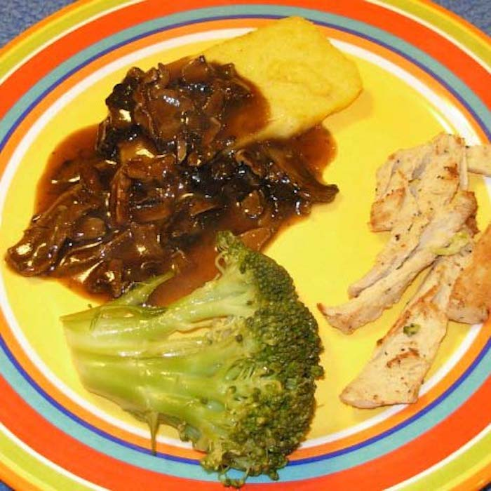 Slow Cooker Polenta with Mushroom Sauce, shown with broccoli and sautéed vegetarian chicken strips.