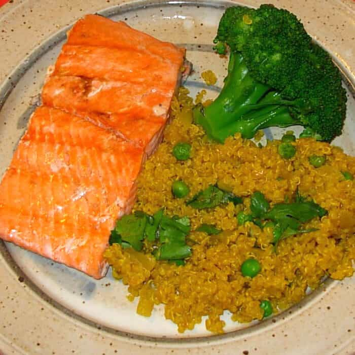 Curried Quinoa, shown with salmon and broccoli.