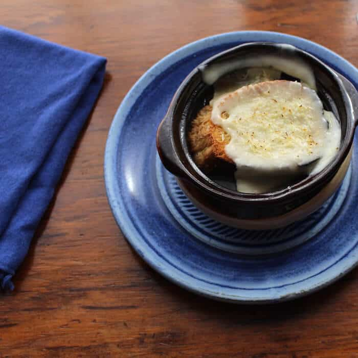 French Onion Soup is topped with French Bread and Cheese. (Beautiful blue plate by Elizabeth Krome.)