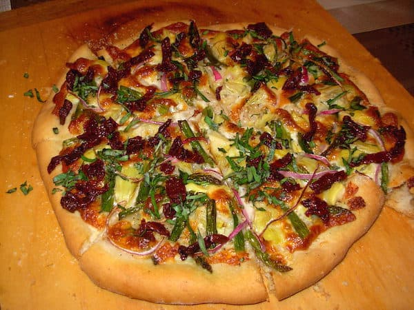 Homemade artisan pizza with artichokes and sun-dried tomatoes.