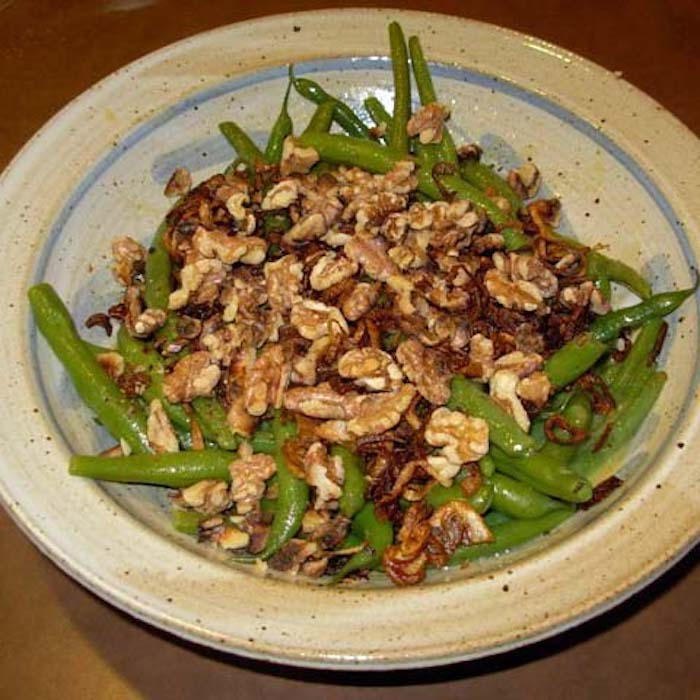 Green Beans, Walnuts and Shallot Crisps side dish has a simple vinaigrette on it.