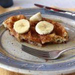 Homemade Basic Waffles (Wheat) are delicious with a bit of syrup and sliced fruit.