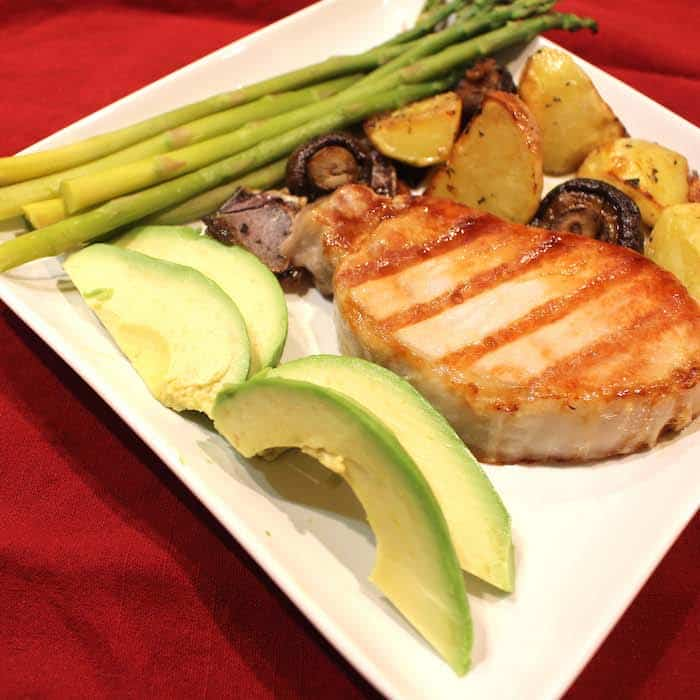A Grilled Pork Chop pairs nicely with grilled potatoes, avocado slices and steamed asparagus.