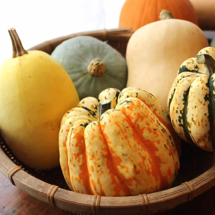 The orange and yellow squash in the front of the basketis a buttercup squash, as is the and the green striped squash to its right. Clockwise from the orange buttercup squash: spaghetti squash, hubbard squash, butternut squash.