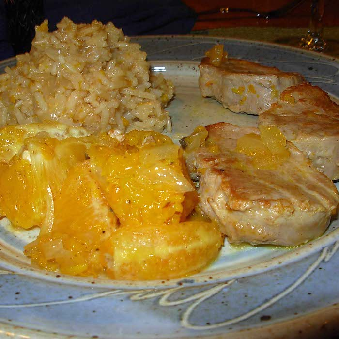 Orange Rice Pilaf, shown with oranges and a pork chop. Oh my. So good. Beautiful plate by Elizabeth Krome at Quail Run Pottery.