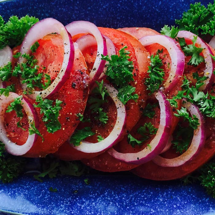 This simple sliced tomato onion salad has a light vinaigrette that is perfect for summer. Beautiful platter by Elizabeth Krome, Quail Run Pottery.