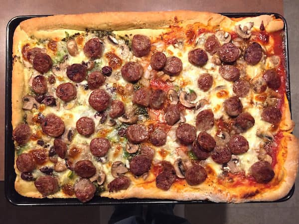 Rolled Crust Pizza: half with red sauce; half with pesto