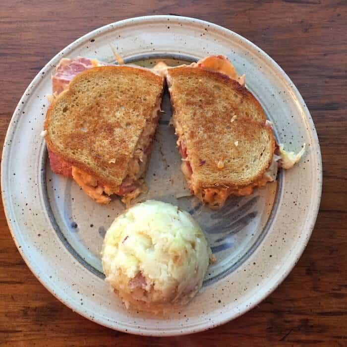 Classic Corned Beef Reuben Sandwich on Rye, shown with Colcannon.