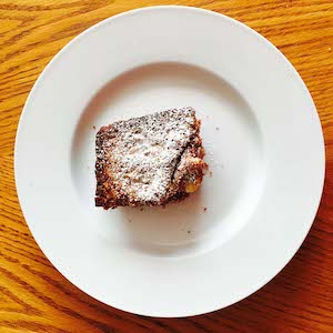 Gluten free dairy free brownie, topped with powdered sugar.