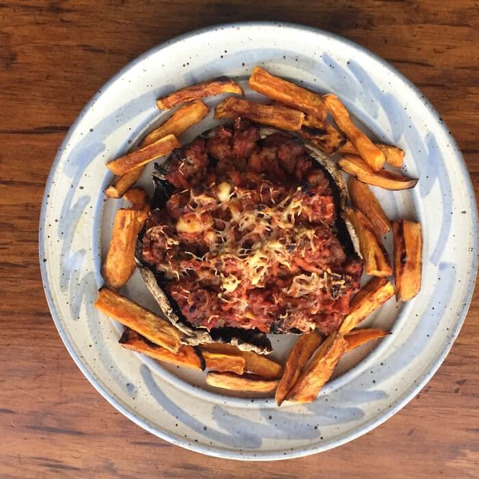 """Pizza burger made with on a portobello mushroom cap and served with roasted sweet potato """"fries."""""""