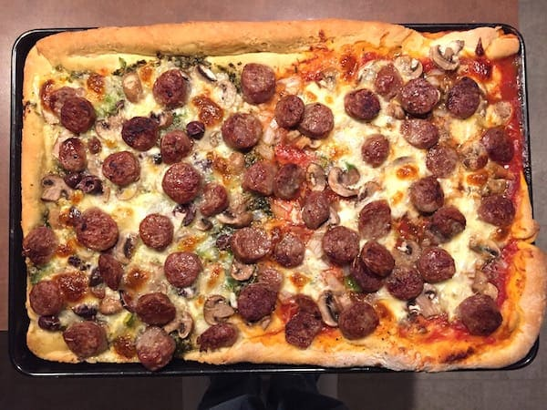 Rolled Crust Pizza made half with red sauce; half with pesto