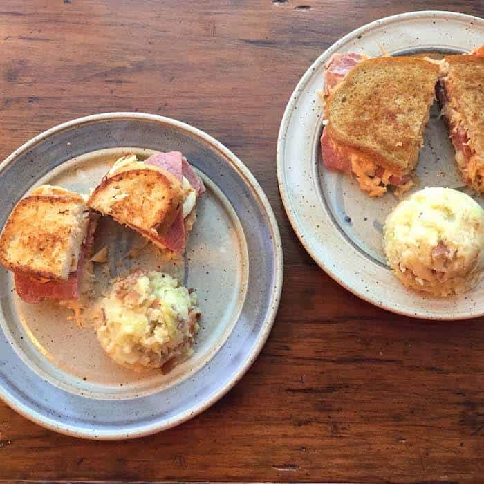 Here are two kinds of Reubens: HalloumiGluten Free Corned Beef Reuben (left) and Classic Corned Beef Reuben (right), both served with Colcannon.