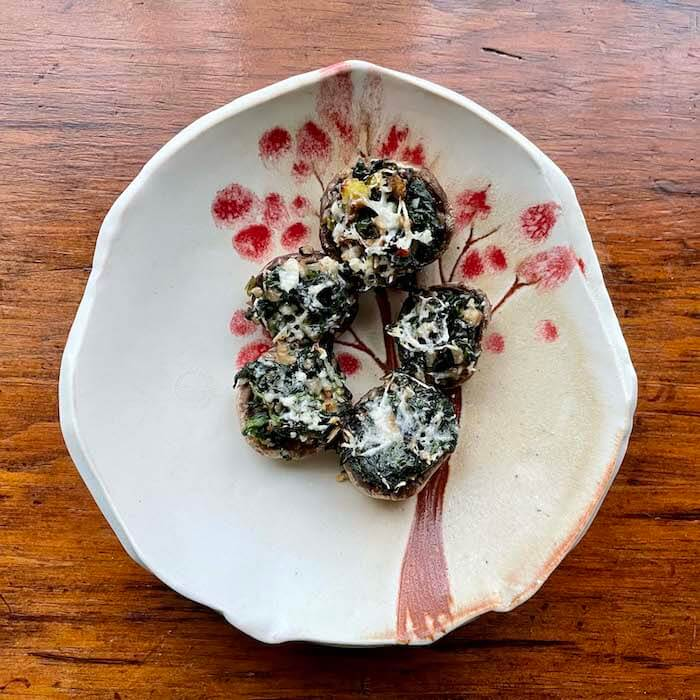 Spinach Stuffed Mushrooms shown on a plate made by potter Kary Haun.