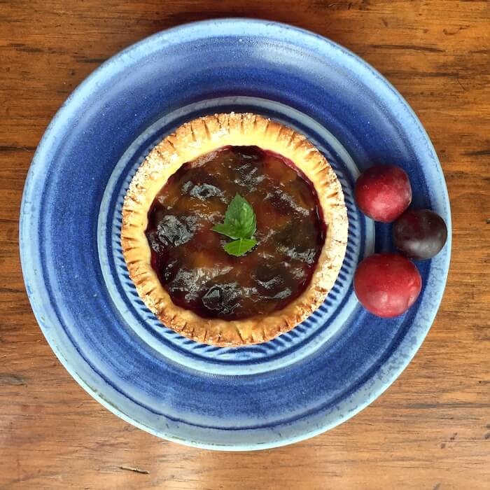 Plum Tart with Gluten Free Crust, shown with sugar plums on a beautiful plate by Elizabeth Krome of Quail Run Pottery.
