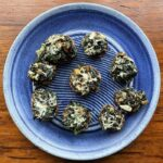 Spinach Stuffed Mushrooms shown on a plate by Elizabeth Krome.